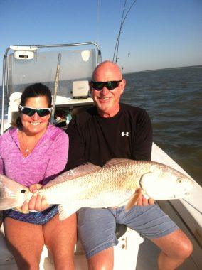 A couple holding a redfish on a fishing charter
